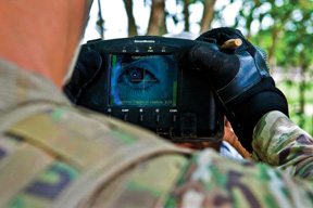 A U.S. paratrooper uses a handheld identity detection device to scan an Afghan man's iris while on patrol in Afghanistan's Ghazni province.