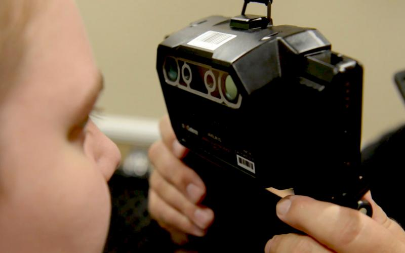 Two people demonstrate how a device is used to capture imagery of irises for the Next Generation Identification (NGI) Iris Service. Credit: FBI