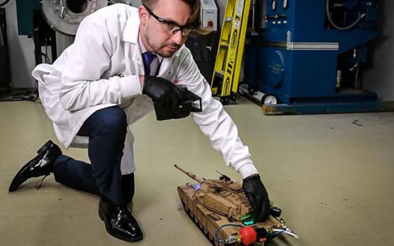 Army researcher Anthony J. Roberts powers a radio-controlled toy tank with hydrogen harvested from a unique chemical reaction. U.S. Army photo by David McNally