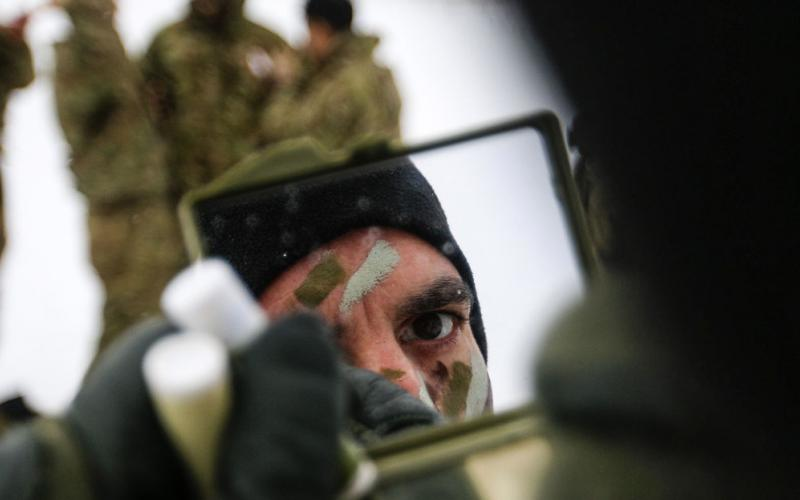 Army Sgt. K.C. Pless applies camouflage paint before a multinational weapons training session with Danish troops in Estonia on March 10 in support of support Operation Atlantic Resolve. As the Army operates in an ever-changing world, the service's military intelligence needs to provide a counter to the evolving threats. Army photo by Spc. Hubert D. Delany III