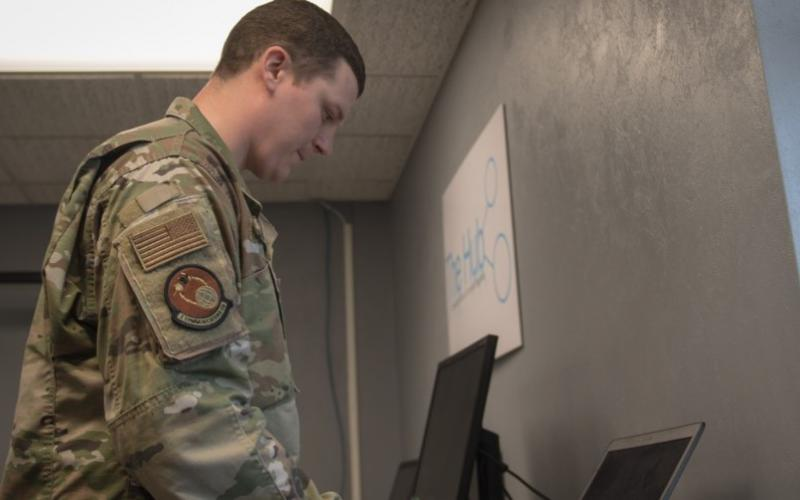 Staff Sgt. Jonathan Witzel, USAF, inspects a customer's laptop on Barksdale Air Force Base, Louisiana on March 20. With the COVID-19 pandemic forcing many Defense Department personnel to work from home, the Defense Information Systems Agency is seeing increased demand for its Cloud-Based Internet Isolation technology. U.S. Air Force photo by Tech. Sgt. Daniel Martinez