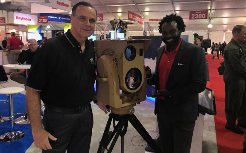 Two Boeing employees, Jerry Drelling (l), external communications, and Rhoan Boucher, weapons programs, Global Sales & Marketing Team, stand next to Boing's compact laser weapon system, known as CLWS. CLWS offers a powerful, yet manportable solution to unmanned aerial vehicle threats, according to the company. Credit: Boeing