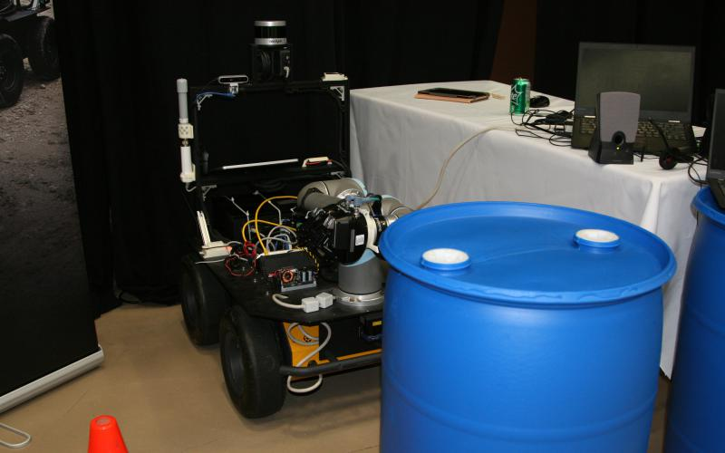 If faced with two potentially dangerous barrels apart in a roadway, this robot will use its sensors and its mechanical arm to determine which one is only partly full. That barrel then will be moved out of the way to clear a safe path for soldiers.