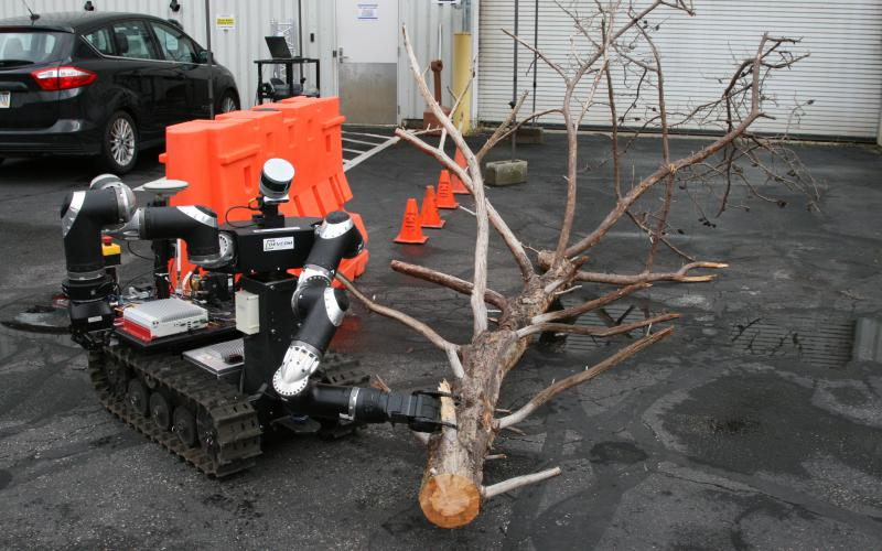An ARL RCTA robot designed to clear paths of obstacles opted to use its clawed arm to drag a large tree limb out of the way rather than attempt to carry it off. Sensors weighed options based on the vehicle's capabilities to determine the best course of action.