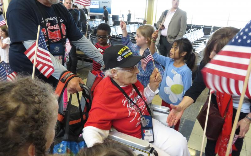 World War II veteran Josephine Renshaw and her Honor Flight Guardian make their way through the path created by hundreds of grateful greeters young and old.
