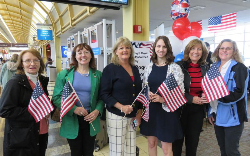 AFCEA staff members plus Washington DC Chapter member Dr. Danielle Zeedick prepare to meet and greet World War II and Korean War veterans arriving at Reagan National Airport from Marion, Illinois.