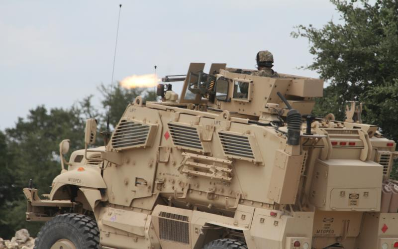 A soldier fires a .50 caliber machine gun on top of a Mine Resistant Ambush Protected (MRAP) vehicle at a range to train for a deployment.