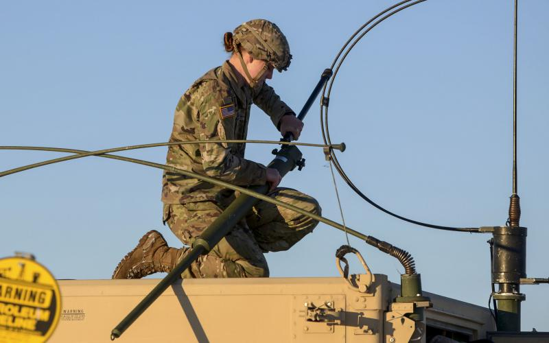 A soldier attaches long-range radio equipment to a Humvee. A GAO report warns that adversaries could take control of the electromagnetic spectrum in the battlespace if the Defense Department doesn't establish effective plans and oversight of its EMS efforts. Credit: U.S. Air Force photo