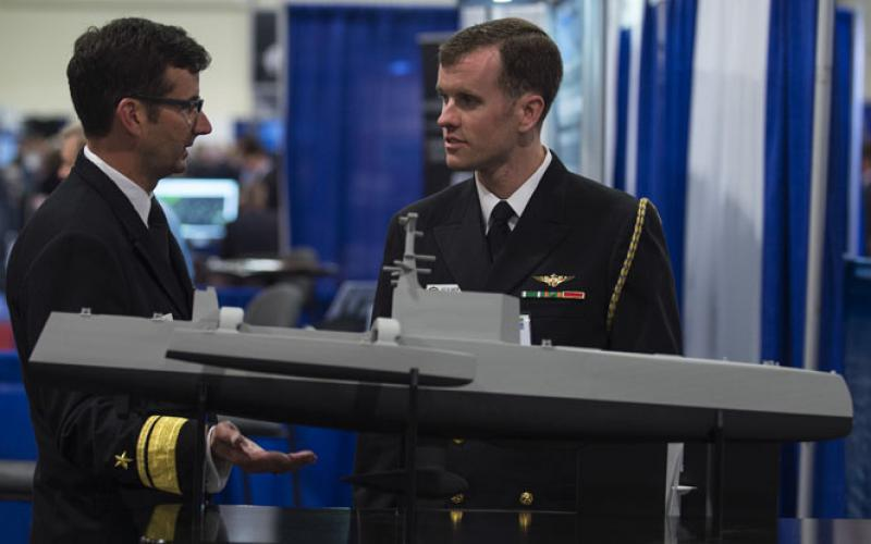 "Rear Adm. Christian ""Boris"" Becker, USN, commander, SPAWAR (l), discusses naval capabilities with another officer while visiting the Office of Naval Research and Naval Research Laboratory  exhibit at the Navy League's Sea-Air-Space Exposition last year. SPAWAR System Command's recent Other Transaction Agreement (OTA) award for its Information Warfare Research Project  will drive key innovative information warfare capabilities to the Navy, Rear Adm. Becker says. Credit: U.S. Navy photo by John F. Williams"