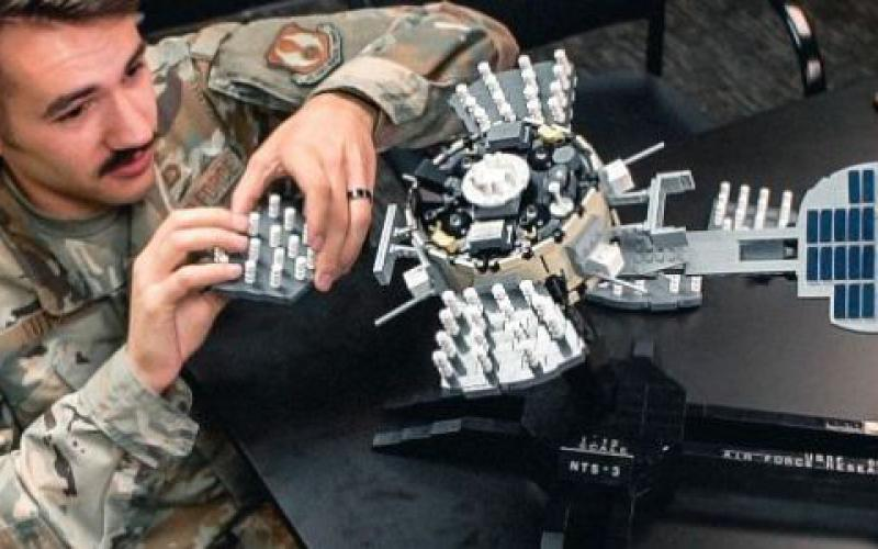 An AFRL engineer works on a Lego model of the Navigation Technology Satellite-3. The AFRL is working on advanced techniques for detecting and mitigating interference to the advanced position, navigation and timing satellite, scheduled to launch in 2022.  AFRL