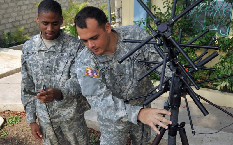 Army soldiers check the setup up of an antenna for voice and data tactical communications in Port-au-Prince, Haiti. While the responsibilities between the Cyber and Signal branches are still evolving, a seven-layer model may be helpful in defining the divide. U.S. Navy photo by Chief Petty Officer Robert J. Fluegel