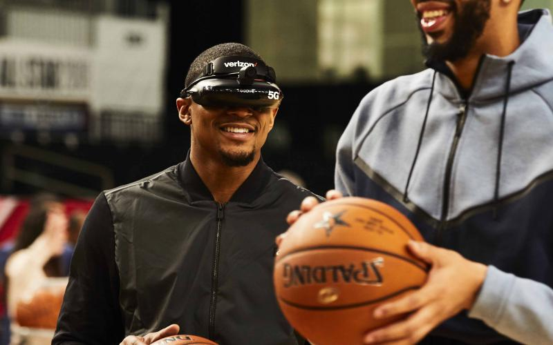 NBA stars Bradley Beal (l) and Anthony Davis use 5G-enabled virtual reality goggles to shoot baskets prior to an NBA All-Star game. Video with extremely low latency will enable 5G users to operate complex machinery from great distances, opening up new work-at-home tasks that previously required on-site presence.  Verizon