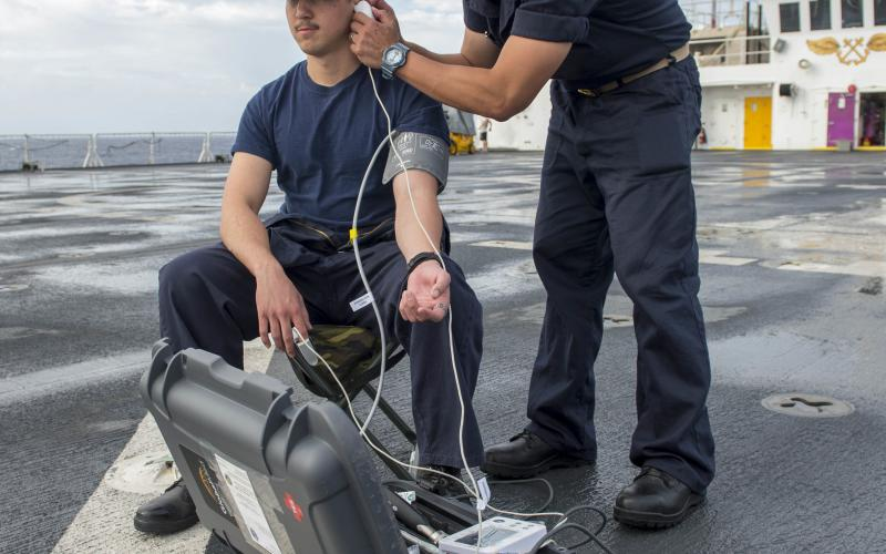 Lt. Cmdr. Art Ambrosio, USN (r), performs an ear examination on Hospital Corpsman 3rd Class Francis Soucie, USN, during the first trial run of a portable telemedicine unit on the flight deck of the U.S. Navy hospital ship USNS Mercy in 2018. This spring, the Mercy served on the U.S. West Coast to provide medical assistance during the COVID-19 pandemic.