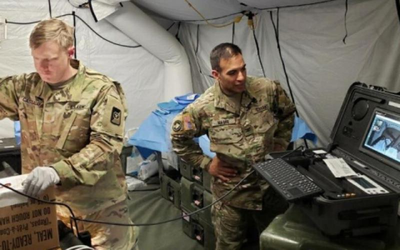 Maj. Ian Cassaday, USA (l), a surgeon with the 250th Forward Surgical Team, utilizes a Telehealth in a Bag kit and a GlobalMed TES to simulate a craniotomy performed by a non-neurosurgeon during testing of virtual health capabilities in the field.  U.S. Army