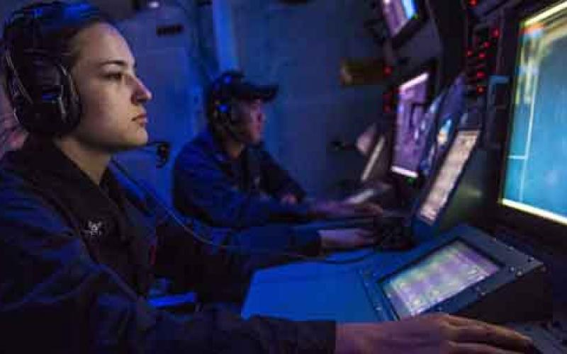 A sonar technician onboard the guided missile destroyer USS Mustin stands watch in the ship's sonar center. With cyberspace being a warfighting domain, the U.S. Navy's information networks are a major target that must be protected and defended proactively.