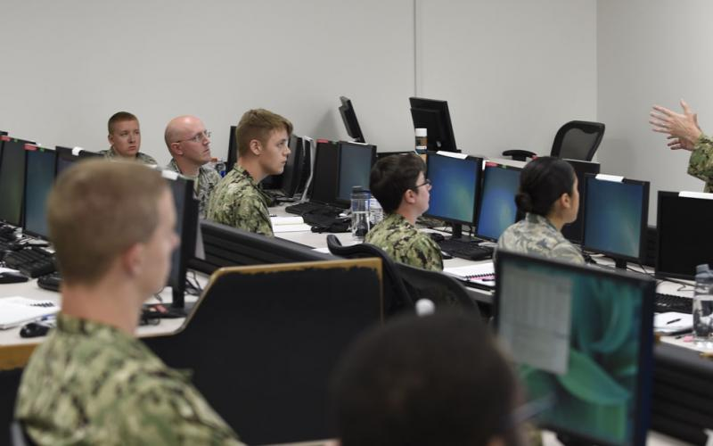 Rear Adm. Timothy White, USN, commander, Cyber National Mission Force, U.S. Cyber Command, shares feedback with students attending the Joint Cyber Analysis course at the Information Warfare Training Command (IWTC), Corry Station, Pensacola, Florida. The Unified Platform will assist members of all services in securing networks by enabling cyber warriors to prosecute full-spectrum cyberspace operations. Credit: Glenn Sircy/Center for Information Warfare Training Public Affairs