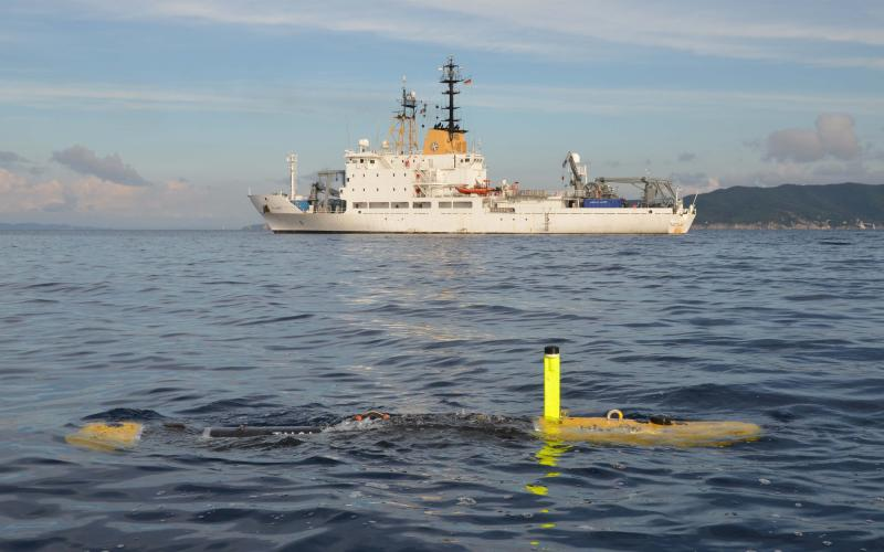 The MUSCLE autonomous vehicle developed by the Centre for Maritime Research and Experimentation, or CMRE, for mine countermeasures works with the NATO Research Vessel Alliance (in the background). The autonomous vehicle is equipped with synthetic aperture sonar.