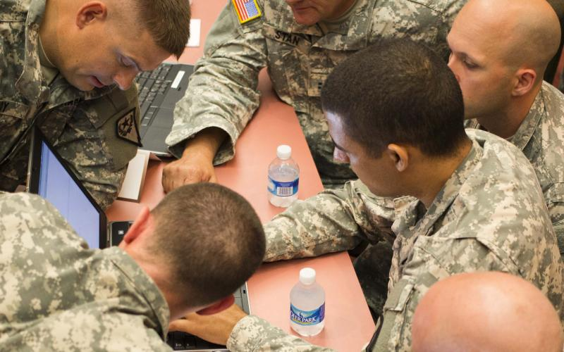 Gathering around a single laptop, soldiers from Team National Guard map out a strategy to win the U.S. Army's Cyber Center of Excellence's multiservice NetWar competition in 2014. The exercise was created to build the cyber operators' capabilities in the new warfighting domain.