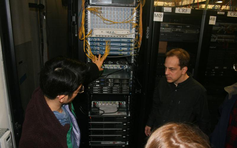Along with computer servers and routers, optical network equipment, supplied to the COSMOS testbed by the University of Arizona, provides fast connectivity between edge cloud computing and radio nodes, explains Tingjun Chen (l), a Columbia University doctoral student, and his professor, Gil Zussman.