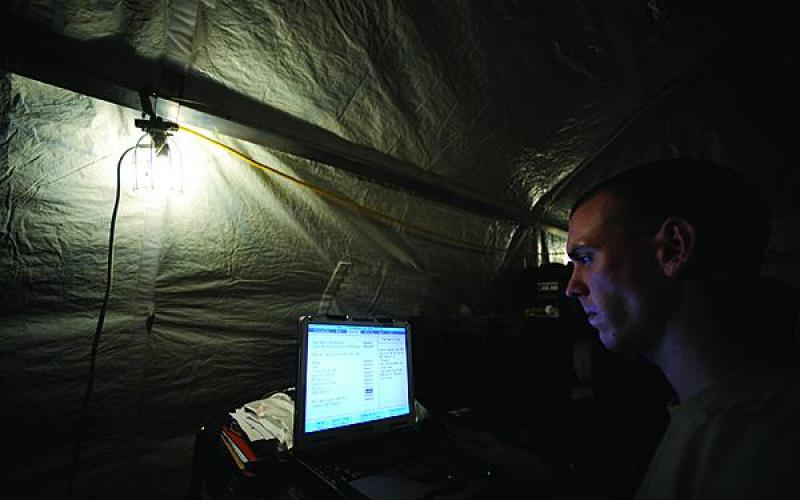 A U.S. Air Force network administrator employs a laptop at Kandahar Airfield, Afghanistan.