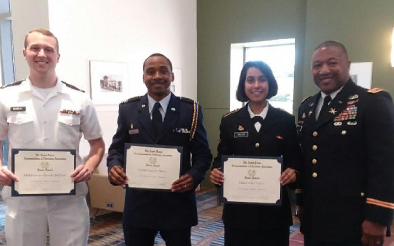 Maj. James Crenshaw, USA, secretary, AFCEA Palmetto Chapter (far r), presents ROTC Honor Awards to University of South Carolina students (l-r) Midshipman Brooks E. McNeal, Naval ROTC; Cadet Leon E. Davis, Air Force ROTC; and Cadet Aditi R. Taylor, Army ROTC.