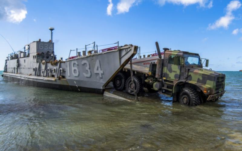 A U.S. Army light medium tactical vehicle departs for the beachfront from a U.S. Naval Landing Craft Utility operating out of the USS Ashland (LSD 48) providing typhoon relief on Saipan, Commonwealth of the Northern Mariana Islands in November 2018. With military activity worldwide, the Army Contracting Command has to meet global demands.  U.S. Air Force photo by Tech. Sgt. Christopher Ruano