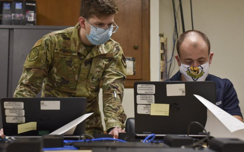 Airman 1st Class Tristan Williams, USAF, 4th Communications Squadron, communications focal point client systems technician (left), and Timothy Leineke, computer support technician for the squadron, examine ways to remotely add computers to the network at Seymour Johnson Air Force Base, North Carolina, in September 2020. DISA is developing robotic process automation solutions to aid such security authorization processes, saving time and workloads.  U.S. Air Force photo by Airman 1st Class Kimberly Barrera
