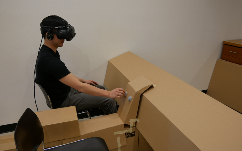 Clement Zheng, doctoral candidate, lecturer and researcher at the University of Colorado Boulder's ATLAS Institute, tests a preliminary project using a cardboard structure combined with virtual reality and a haptic interface. Leithinger, who also directs the ATLAS Institute's THING Lab, emphasizes that fast prototyping abilities using inexpensive materials can drive innovation in such interfaces.