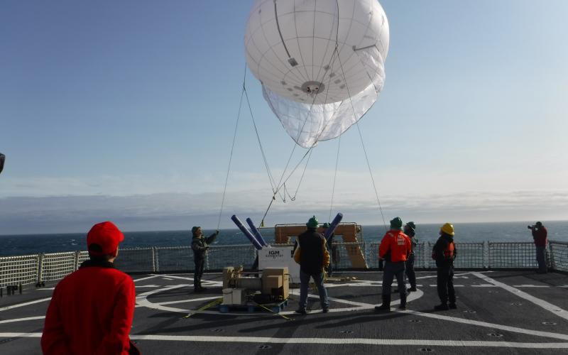 A Coast Guard test team begins deployment of an aerostat off the flight deck of the U.S. Coast Guard Cutter Healy in the Arctic region. This year, researchers are evaluating a smaller version with higher wind capabilities. The aerostat will carry a communications package that will allow contact with an unmanned aerial vehicle that has flown beyond the line of sight.