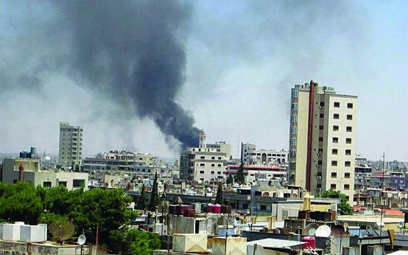 Smoke drifts into the sky from buildings and houses hit by shelling in Homs, Syria. Many Jihadi fighters leaving Syria will funnel through the Balkans and may pose a threat to other parts of the world.