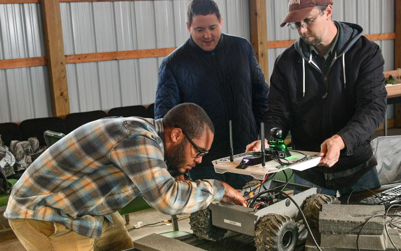 (From left) Army C5ISR Center employees Donovan Sweet, Rob Beckinger and Dan Lenhardt assess a robotic vehicle for the C4ISR Modular Autonomy project at Camp Grayling, Michigan. Under the Army vision, multiple robotic vehicles may be remotely controlled by the crew of a manned combat vehicle. Credit: Conrad Johnson, Army public affairs official​