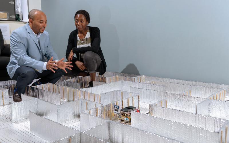 Raheem Beyah, the Motorola Foundation professor in Georgia Tech's School of Electrical and Computer Engineering, and Celine Irvene, a student at Georgia Tech, watch the HoneyBot progress through a maze. Credit: Rob Felt