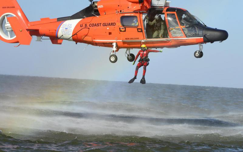 A U.S. Coast Guard rescue swimmer jumps out of an MH-65 Dolphin helicopter during a training exercise. Artificial intelligence-driven human forensics technology has helped the maritime service track down people accused of making hoax mayday calls, which cost tens of thousands of dollars and distract from the Coast Guard's mission. Coast Guard photo