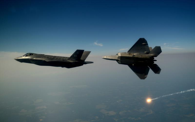 An F-35A Lightning II joint strike fighter and an F-22A Raptor soar over the Emerald Coast. Some nations have reduced the number of F-35s they intend to purchase.