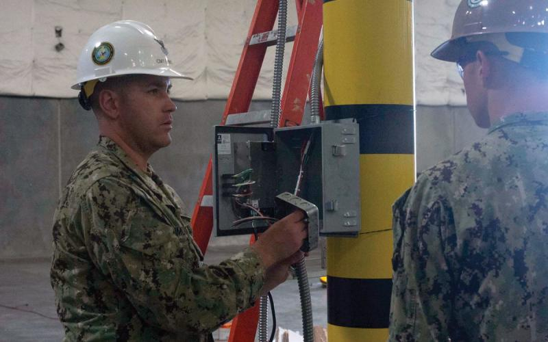 Construction Mechanic 1st Class Jay Emmons, USN, Naval Construction Group 1, instructs Seabees on placement of material within the junction box that will provide power to several of the 240 24-volt charging reels for Civil Engineering Support Equipment (CESE). These grid/reel systems charge and de-sulfate batteries, enabling the CESE to be operationally ready around the clock. Credit: Engineering Aide 1st Class Heather Salzman, USN