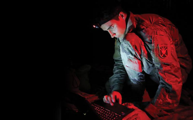 A U.S. Army John F. Kennedy Special Warfare Center and School student uses a PDA-184 computer during nighttime antenna training at Fort Bragg, North Carolina. The training qualifies students in the high frequency communications module to be proficient in making, installing, operating and maintaining short-, medium- and long-range antennas to communicate at long distances. Credit: K. Kassens