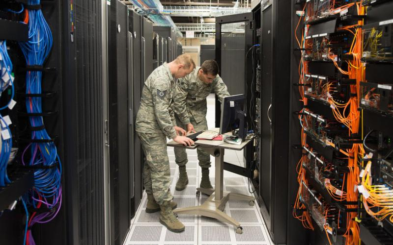 Tech. Sgt. David Mooers (l) and Senior Airman Mario Lunato, 2nd System Operations Squadron system administrators, access one of the core servers in the 557th Weather Wing enterprise at Offutt Air Force Base, Nebraska. The wing is employing specialized cybersecurity crews on top of other cyber defenses to protect weather intelligence. U.S. Air Force photo by Paul Shirk