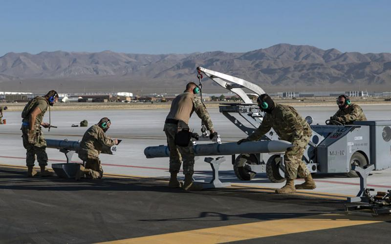 Airmen from the 140th Maintenance Group prepare to load munitions onto an F-16 Fighting Falcon from the 120th Fighter Squadron at a simulated austere base during the Advanced Battle Management System (ABMS) exercise on Nellis Air Force Base, Nevada, in September. The exercise at Nellis tested the digital integration of the U.S. Air Force's ABMS with other weapons and communications systems in a Joint warfighting environment. Credit: Air Force photo by Tech. Sgt. Cory D. Payne