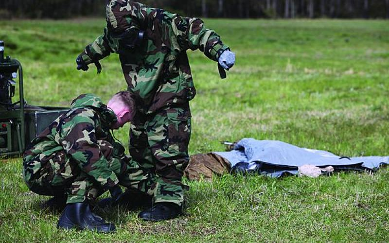 Marines at Camp Lejeune, North Carolina, assist each other in donning chemical and biological protection suits. Scientists are working to develop new fabrics that will minimize the need for the heavy, uncomfortable suits.