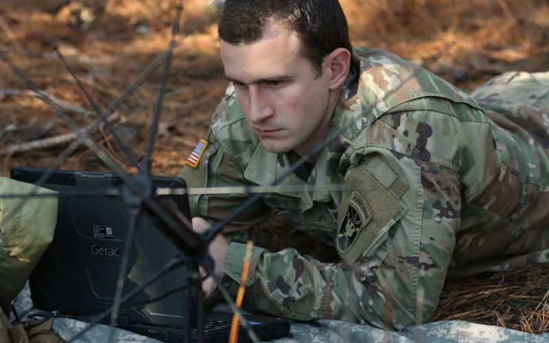 A student assigned to the U.S. Army John F. Kennedy Special Warfare Center and School, who is in the Special Forces Communications Sergeant course, trains using a PDA-184 computer and an AN/PRC-117G satellite radio during training at the Yarborough Training Complex at Fort Bragg, North Carolina.  U.S. Army photo by K. Kassens