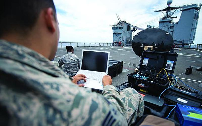 Senior Amn. Xavier Rubio, USAF, tests a satellite communications dish aboard the amphibious dock landing ship USS Pearl Harbor.
