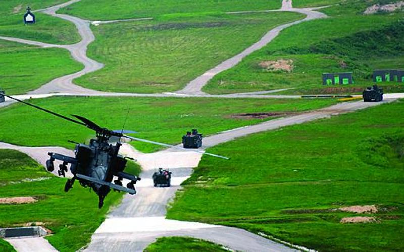 Pilots of an AH-64D Apache fly over soldiers of 1st Battalion, 27th Infantry Regiment, 2nd Stryker Brigade Combat Team, 25th Infantry Division, while preparing to deliver an attack on enemy targets at the Digital Multipurpose Range Complex during Wolfhound Maul.