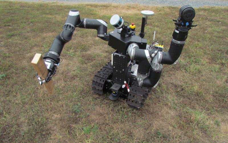 A small robot grasps a piece of wood as a test of its ability to remove obstacles from its path. The ARL's testbed at Graces Quarters will enable researchers to test robotic capabilities against real-world scenarios such as fallen tree limbs or artificial barricades in the field.  U.S. Army photo