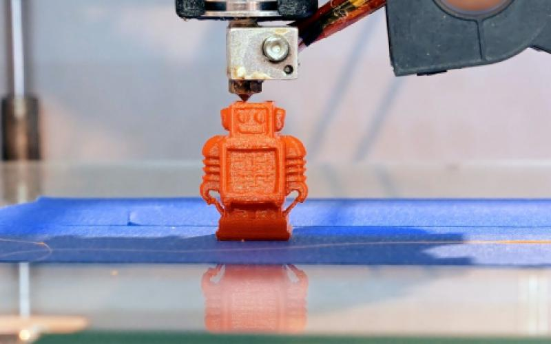 An automatic 3D printer creates a small robot figure on an additive manufacturing platform. The technology is ideally suited for custom manufacture of small parts and items.  Shutterstock/Kyrylo Glivin
