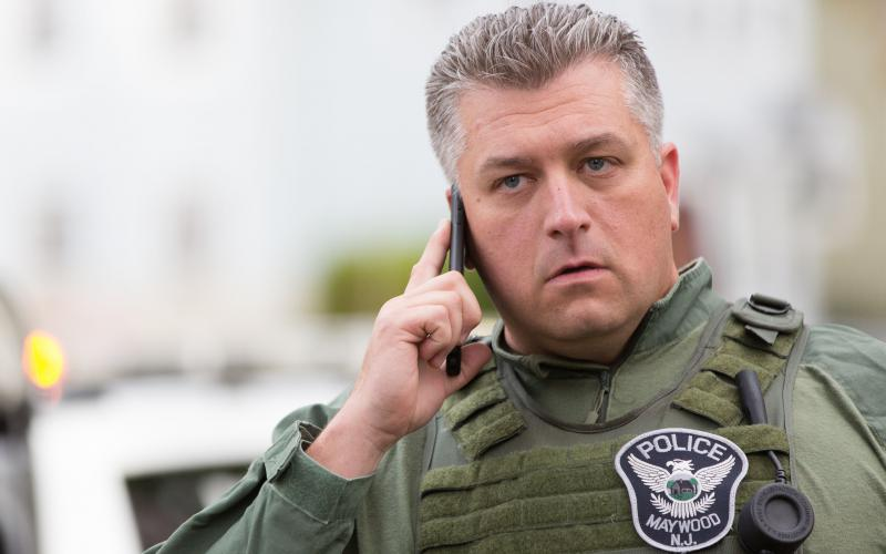 A police officer uses a smartphone at a crisis scene. The introduction of broadband devices is creating interoperability problems for emergency responders used to conventional radio communications.