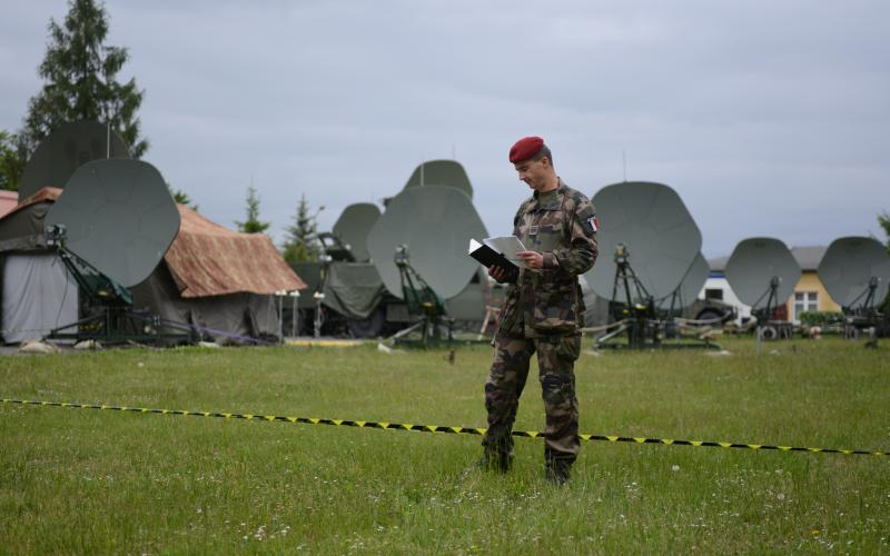 A French officer reviews notes in front of communications antennas during NATO's Steadfast Cobalt 15 exercise, held from late May to early June in Poland. The exercise evaluated communications and information system requirements for the NATO Response Force, which will be stood up next year.