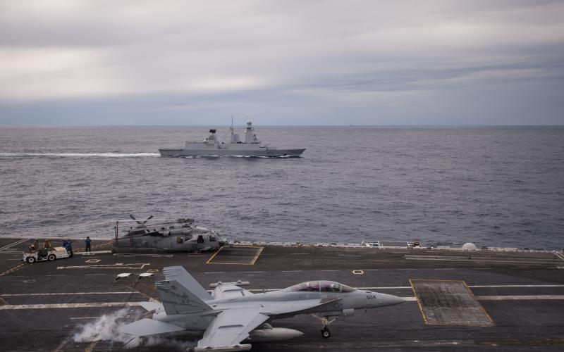 A U.S. Navy EA-18G Growler electronic warfare (EW) aircraft lands on the flight deck of the USS George H.W. Bush during an international exercise that includes the French navy frigate Forbin (rear). Naval exercises with allies and partners help develop ways of integrating EW and related warfighting activities.
