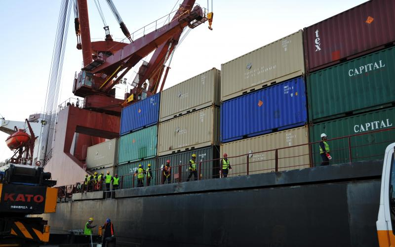 Workers prepare to offload shipping containers from a U.S. Military Sealift Command ship in Kuwait. Foreign cyber intrusions into commercial shipping networks have allowed cybermarauders access to significant information about cargoes and schedules.