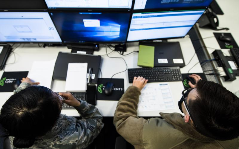 Senior Airman Rose Li, USAF (l), and Airman 1st Class Eric Gardella, USAF, 86th Communications Squadron wing cyber readiness technicians, monitor malicious network activity during exercise Tacet Venari at Ramstein Air Base, Germany, in 2020 to prepare local cyber defenders in safeguarding critical technological infrastructures. U.S. Air Force photo by Staff Sgt. Devin Boyer