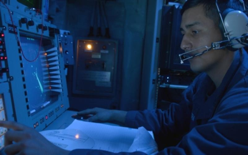 A U.S. Navy cryptologic technician monitors the electromagnetic spectrum of air and surface contacts in the combat information center aboard the guided-missile destroyer USS Ramage in 2014.